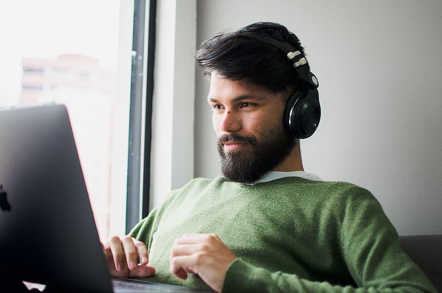 man-wearing-headphones-while-looking-at-macbook